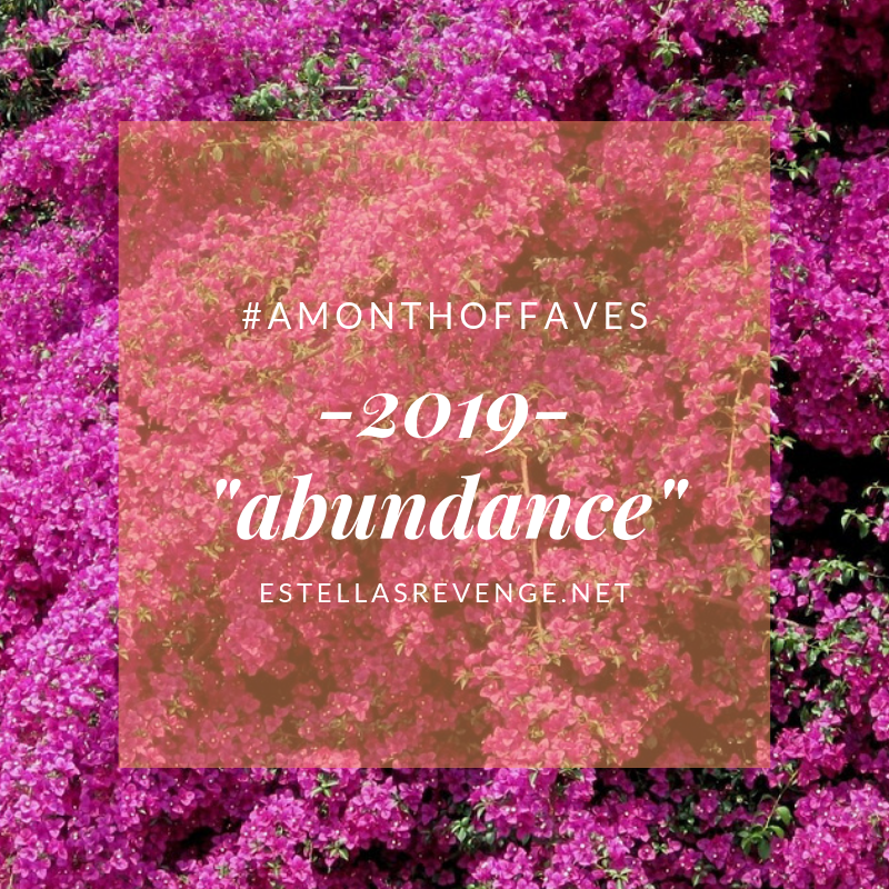 A background profusion of pink flowers. Overlaid text reads: #amonthoffaves -2019- abundance with the estellasrevenge.net link at the bottom of the graphic.