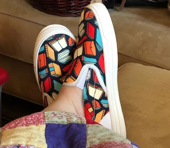 A pic of my feet bedecked in my new book shoes. Two feet, crossed, legs covered in a quilt. The shoes are slip-on style with black print, orange, yellow, and blue book print, and white soles and edging.